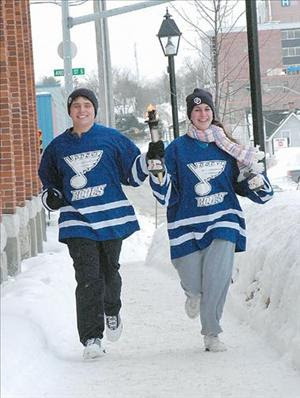 Kyle Frederickson and Julianne Tersigni carry the Torch of Life down Colborne Street in Orillia, Canada yesterday.