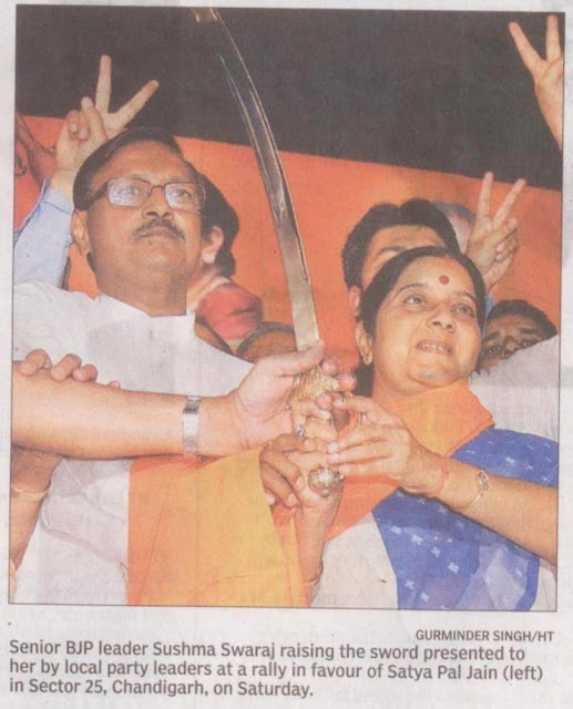 Senior BJP leader Sushma Swaraj raising the sword presented to her by local party leaders at a rally in favour of Satya Pal Jain........