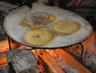 A color photo of tortillas cooking on an iron comal.