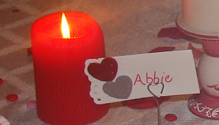 A red lit candle with a name tag next to it.