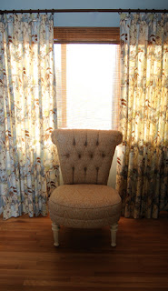 Chair in front of a window with curtains partly drawn