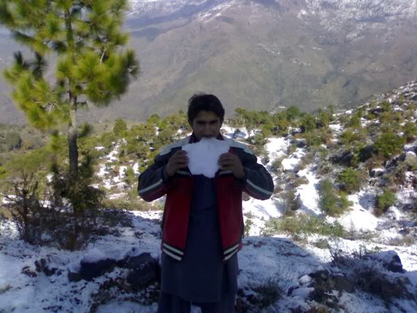 A guy holding a piece of snow at winter season in Darband