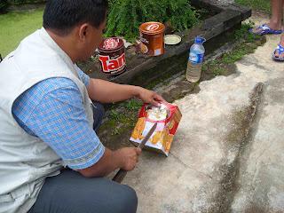 Lubangi sekeliling kaleng roti dengan menggunakan parang