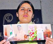 Seeking justice: Sabra Khan shows her husband's photographs at a press conference on Monday (Picture by IMTIYAZ KHAN).