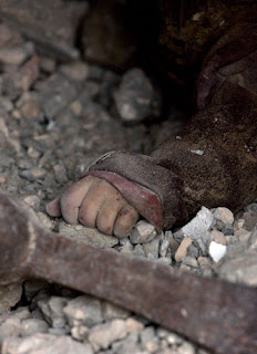 A dead child's hand is visible beneath the rubble of a building in Gaza.