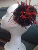 Flor de organza negra con plumas rojas: un bonito detalle para una boda de noche.