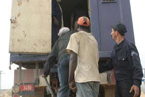 Migranti caricati sui camion della polizia per l'espulsione