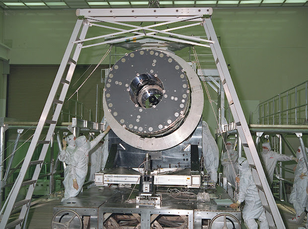 CXO's High Resolution Mirror Assembly (HRMA) being removed from the test structure in the X-Ray Calibration Facility (XRCF) at the Marshall Space Flight Center (MSFC).