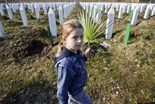 A Bosniak girl carries a leaf to decorate a grave of her relative buried at a cemetery in Potocari among other victims of the 1995 Serb massacre of 8,000 Muslims in the former U.N. 'safe area' Srebrenica February 24, 2007.