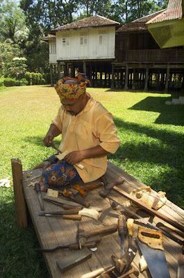 Malay man dressed in traditional garment making a traditional keris in a traditional Malay kampong
