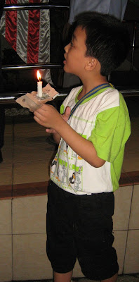 brave little boy with lighted candle to protest the grossly unjust ISA