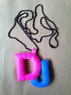 Kalung dari boneka flanel berbentuk huruf. Bisa inisial nama kamu maks