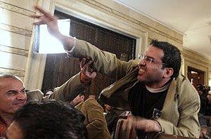 Montazer al Zaidi forcejea con los agentes de seguridad luego de tirara sus zapatos a Bush
