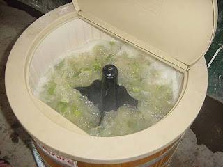 Homem utilizando máquina de lavar pra fazer caipirinha