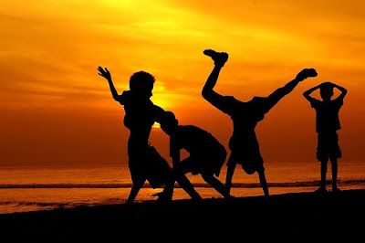 Children playing during a sunset on a beach, having fun.
