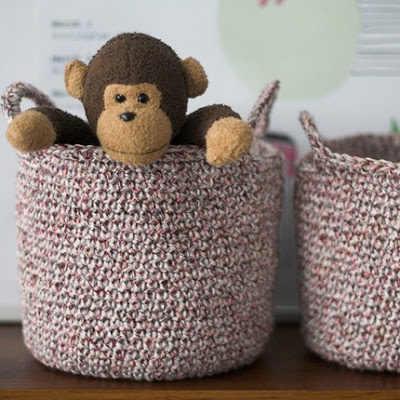 two small pink baskets; one has a stuffed monkey inside