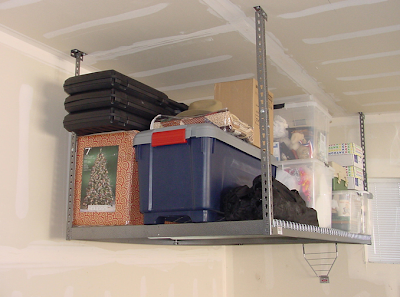 overhead ceiling storage racks in garage, loaded with stuff