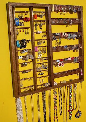 wall jewelry organizer, loaded with earrings and necklaces