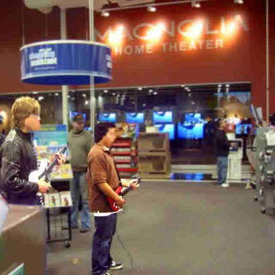 playing some sort of rock star guitar playing game at BEST BUY