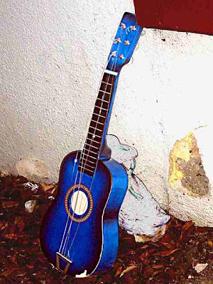Small Blue Guitar Leaning Against Wall