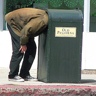 Old Pasadena trash can is inspected by a homeless person