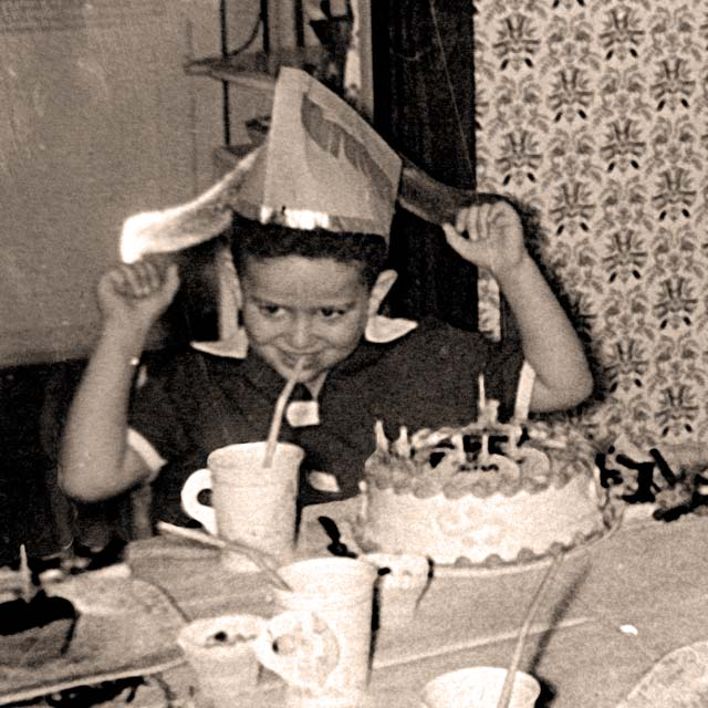 David Ocker wearing a party hat on his fifth birthday in 1956 with birthday cake