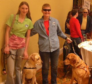 Picture of Toby & I, with Kathy Champion & Angel. Both dogs are staring straight at each other. Angel is dark yellow