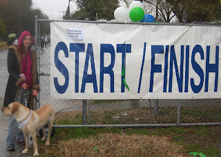 Picture of Toby and I with the Start/Finish sign. I'm looking at the camera, Toby's watching a dog
