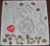 Picture of Toby's pawprint stone. Which has his pawprint in it, and also his dog tag.