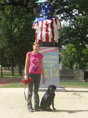 Picture of Rudy in a sit-stay in coat beside me, we are in front of a statue at the USNA