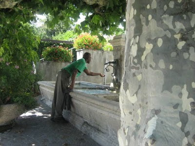 Uche drinks from a fountain.