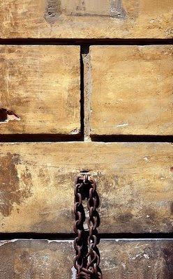 Parede com blocos de construção bem definidos e uma corrende de ferro, supostamente para prender animais