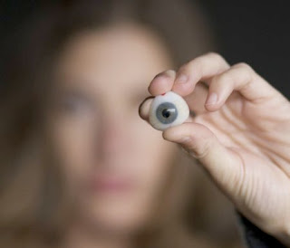 photo is of a woman holding a fake eye ball which contains a web cam. the eye ball and her hand is in focus while her face is blurred in the background