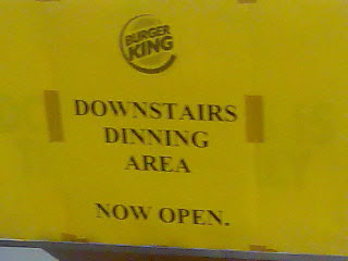 A Burger King sign reading Downstairs Dinning Area Now Open