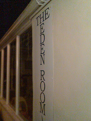 A sign for 'The Eden Room', with 'The' running across and 'Eden Room' underneath it running down