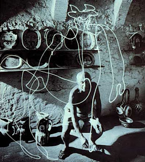 Photograph of Picasso drawing a bull in light