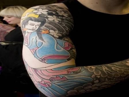 Tattoo of a Japanese girl surrounded with flowers on arm