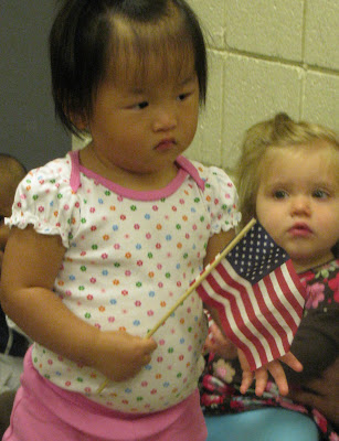photo of: Toddlers wave the American Flag during Author Visit with Debbie Clement