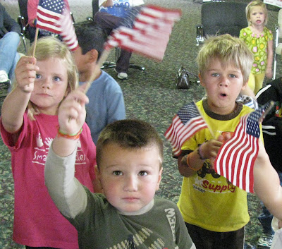 photo of: Preschool Children wave Flag during Author Visit with Debbie Clement