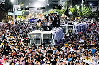 Protesters climb on top of police buses