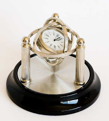 small desk clock on a black base with silver posts and swinging arms