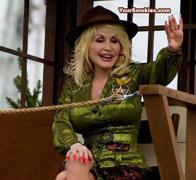 Dolly Parton all dolled up like a national park ranger from a Vegas show on a float celebrating the Smoky Mountains national parks 75th anniversary