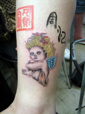 A angel tattoo on the leg with blonde hair and blue wings