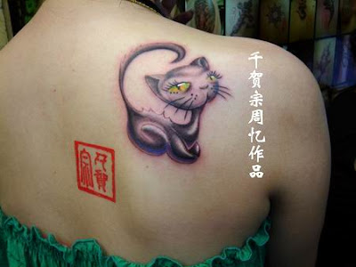 A kitty tattoo on the back with very big and bright eyes