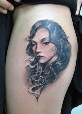 A girl's portrait tattoo on the arm