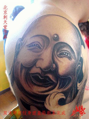 smiling Buddha tattoo on the arm