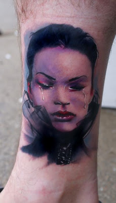 A portrait tattoo on the leg featuring a crying girl