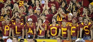 USC college football fans spell out the word playoffs with crimson and yellow body paint