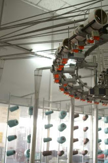 image of a factory machine with dozens of bobbins of thread leading into