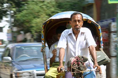image of a rickshaw driver driving with his eyes closed in front of a luxury car.